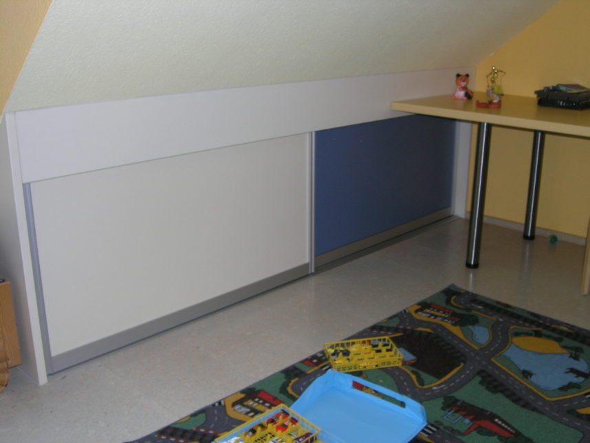 farbiges Schiebetürenregal im Kinderzimmer in der Dachschraege