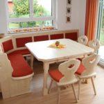 Eckbank in schönem hellen Holz mit rotem Stoff